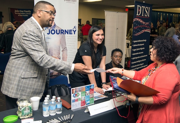 A company recruiter hands information to a visitor on a career opportunity at the Hiring Heroes Career Fair March 21 in the Sam Houston Community Center at Joint Base San Antonio-Fort Sam Houston. At the fair, transitioning, ill, injured and wounded service members, veterans and military spouses got to talk to representatives from employers, companies and governmental agencies on career opportunities.