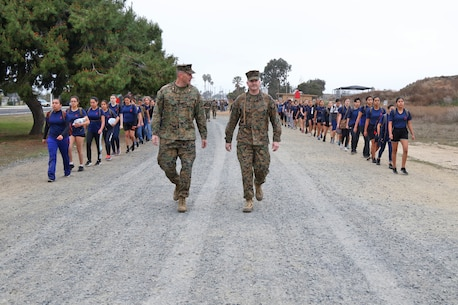 Maj. Adam Taylor, commanding officer of Marine Corps Recruiting Station Orange County, and Sgt. Maj. Jason Politte, the station sergeant major, lead their female poolees to Edison Range during an annual function at Marine Corps Base Camp Pendleton, Mar. 10, 2018. This function brought together young women from across southern California to experience aspects of recruit training in order to provide insight and understanding as to what they'll endure at the depot for 13 weeks. Roughly nine percent of women serve in the United States Marine Corps, the smallest percentage of females in any branch of service. This makes it very important to bring these young women together and learn about specific aspects of life as a Marine, such as hair, hygiene, physical fitness and culture.