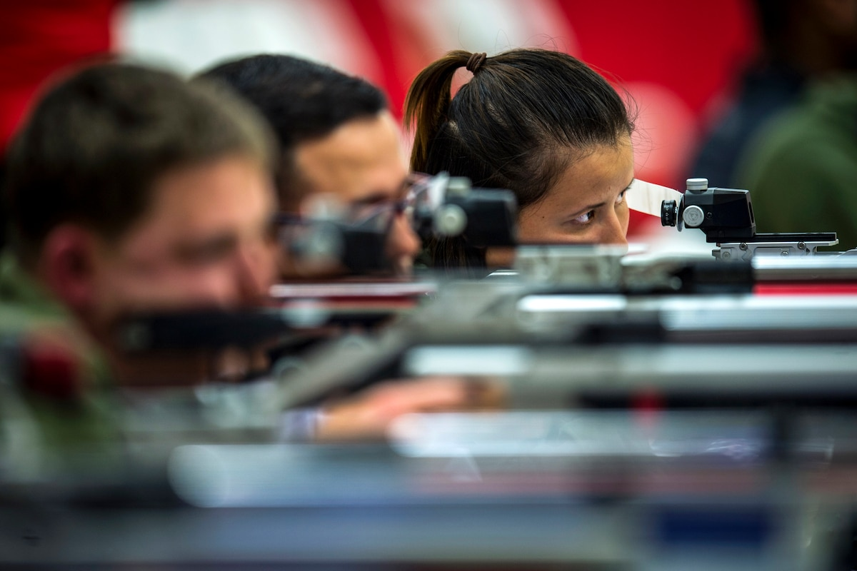A Marine stares while aiming an air rifle on a firing line with fellow athletes.