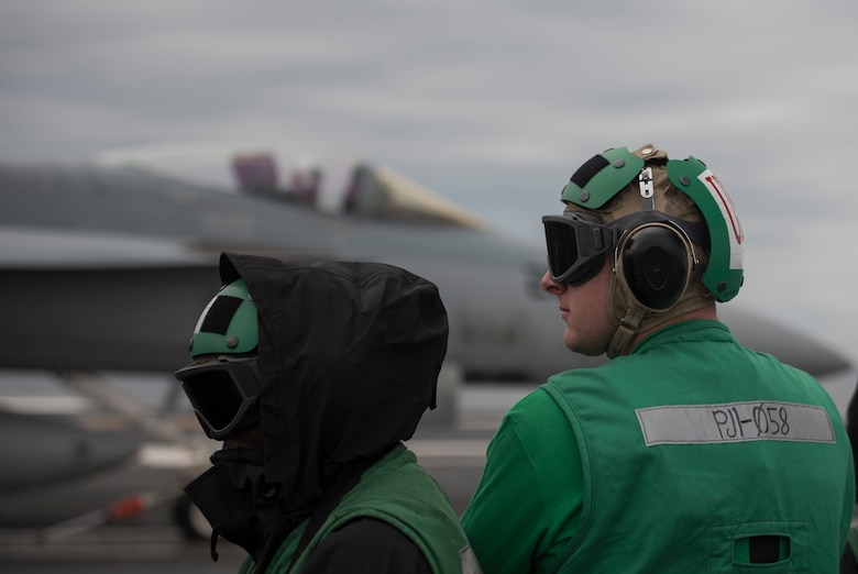U.S. Air Force 1st Lieutenant Sean Duval, 33rd Maintenance Squadron maintenance operations officer, right, stands near the bow catapults during flight deck operations March 19, 2018, on the Nimitz-class aircraft carrier USS Abraham Lincoln (CVN-72). Duval participated in a maintenance officer exchange with a member of Strike Fighter Squadron (VFA) 101. The exchange gave Duval useful insight into Navy maintenance operations and helped him connect to his families history in the U.S. Navy. (U.S. Air Force photo by Staff Sgt. Peter Thompson/Released)