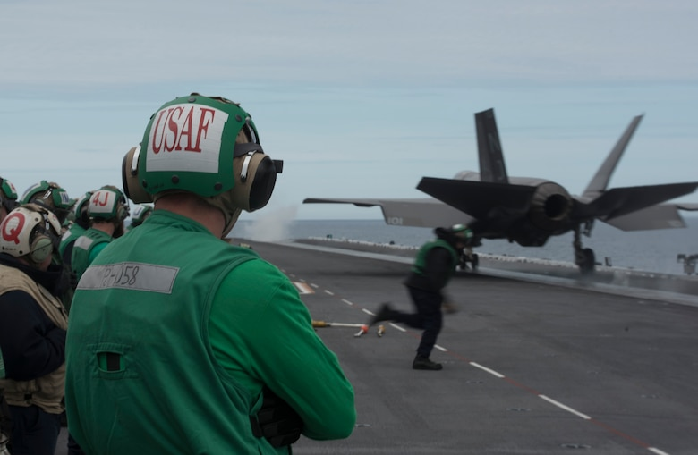 U.S. Air Force 1st Lieutenant Sean Duval, 33rd Maintenance Squadron maintenance operations officer, stands near the bow catapults as an F-35C Lightning II assigned to Strike Fighter Squadron (VFA) 101 is launched March 19, 2018, on the Nimitz-class aircraft carrier USS Abraham Lincoln (CVN-72). Duval plans to use what he learned during his maintenance officer exchange to help improve his unit back at Eglin Air Force Base, Fla. (U.S. Air Force photo by Staff Sgt. Peter Thompson/Released)