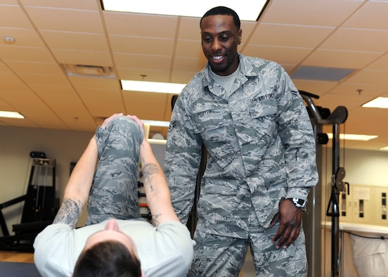 A male standing in a room with exercise equipment helps another male stretch.