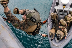 A Marine climbs a rope ladder over water, as troops stand by in a rubber boat below.