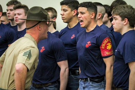 Sgt. Jordan Brown, drill instructor, 1st Recruit Training Regiment, yells commands at Skylar Popillion, a Gilbert, Iowa, native and enlistee in the Marine Corps during a Drill Instructor Family Night at Events Center West in West Des Moines, Iowa, March 23, 2018. Marine Corps Recruiting Command hosts the family nights to better prepare both parent and enlistee prior to attending Marine Corps Recruit Training. (Official U.S. Marine Corps photo by Sgt. Levi Schultz)