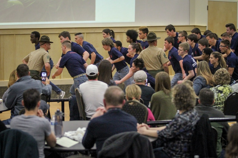 Individuals who recently enlisted in the Marine Corps attempt to follow orders from drill instructors while their families look on during a Drill Instructor Family Night at Events Center West in West Des Moines, Iowa, March 23, 2018. Marine Corps Recruiting Command hosts the family nights to better prepare both parent and enlistee prior to attending Marine Corps Recruit Training. (Official U.S. Marine Corps photo by Sgt. Levi Schultz)
