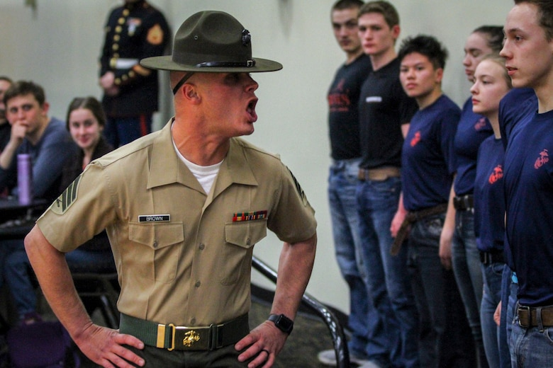 Sgt. Jordan Brown, drill instructor, 1st Recruit Training Regiment, yells commands to individuals who have recently enlisted in the Marine Corps during a Drill Instructor Family Night at Events Center West in West Des Moines, Iowa, March 23, 2018. Marine Corps Recruiting Command hosts the family nights to better prepare both parent and enlistee prior to attending Marine Corps Recruit Training. (Official U.S. Marine Corps photo by Sgt. Levi Schultz)