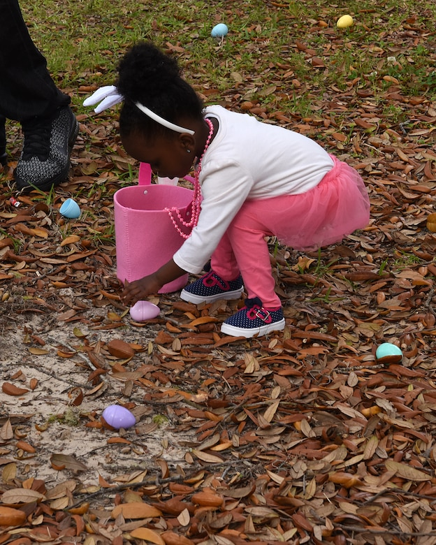 Tauryn Lennon, daughter of U.S. Air Force 2nd Lt. Taurean Lennon, 333rd Training Squadron Undergraduate Cyberspace Training student, picks up plastic eggs during Easter in the Park egg hunt at Marina Park March 24, 2018, on Keesler Air Force Base, Mississippi. The event festivities also included a parade, arts and crafts and informational booths. (U.S. Air Force photo by Airman 1st Class Suzie Plotnikov)