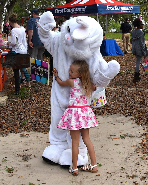 Makai Surber, daughter of U.S. Air Force Master Sgt. Chontee Surber, 81st Dental Squadron clinical flight chief, takes a picture with the Easter bunny during Easter in the Park at Marina Park March 24, 2018, on Keesler Air Force Base, Mississippi. The event festivities included a parade, an Easter egg hunt, arts and crafts and informational booths. (U.S. Air Force photo by Airman 1st Class Suzie Plotnikov)