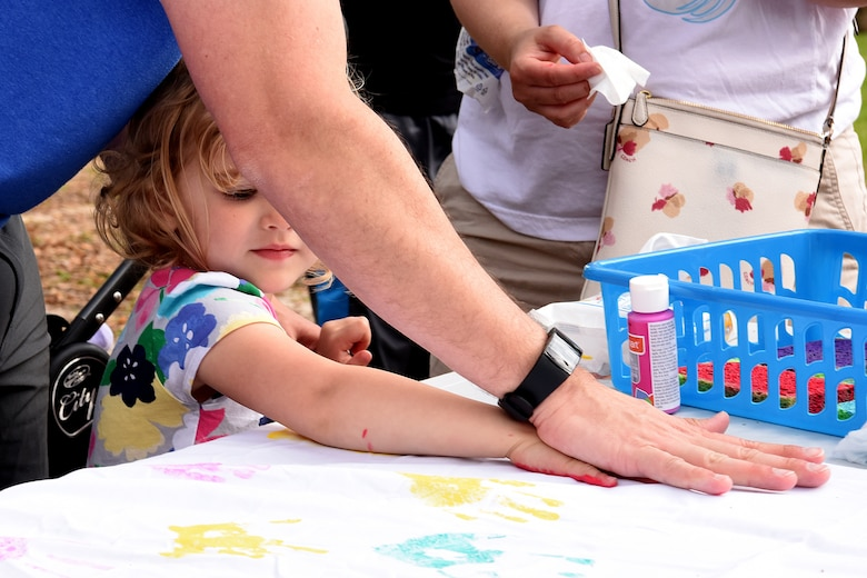 U.S. Air Force Lt. Col. John Eck, 2nd Air Force director of staff, and his daughter, Natalie, paints a handprint during Easter in the Park at Marina Park March 24, 2018, on Keesler Air Force Base, Mississippi. The event festivities included a parade, an Easter egg hunt, arts and crafts and informational booths. (U.S. Air Force photo by Airman 1st Class Suzie Plotnikov)