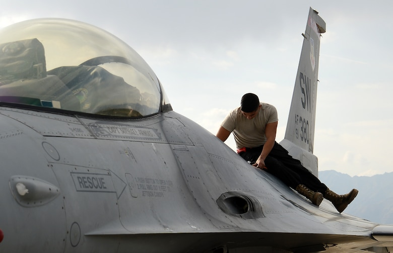 Senior Airman Kevin Zaragoza, 455th Expeditionary Aircraft Maintenance Squadron F-16 Fighting Falcon crew chief, inspects the air refueling door during his preflight inspection Mar. 20, 2018 at Bagram Airfield, Afghanistan.