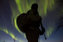 Marine with Marine Rotational Force-Europe prepares to conduct a mountainous assault on enemy position as the northern lights shine above during the field training exercise portion of Exercise White Claymore near Bardufoss, Norway, February 15, 2018. White Claymore is a U.K. Royal Marines-led training in northern Norway that focuses on winter warfare including training on movement in adverse terrain and over snow, and training in defensive and offensive operations in winter conditions. (U.S. Marine Corps photo by SSgt. Marcin Platek/Released)