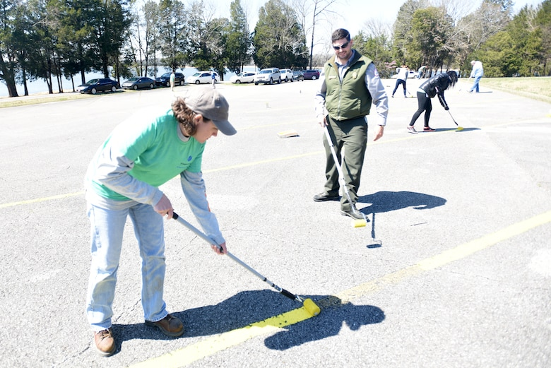 Lisa Parmelee, supply planning team leader with VF Solutions, paints parking spot stripes while volunteering for an early Earth Day clean-up event March 22, 2018 at Seven Points Campground on the shoreline of J. Percy Priest Lake in Hermitage, Tenn. Park Ranger Carter Robinson stands by to assist. Sixty VF Solutions employees partnered with the U.S. Army Corps of Engineers Nashville District to spruce up the popular campground ahead of the 2018 recreation season. (USACE photo by Lee Roberts)
