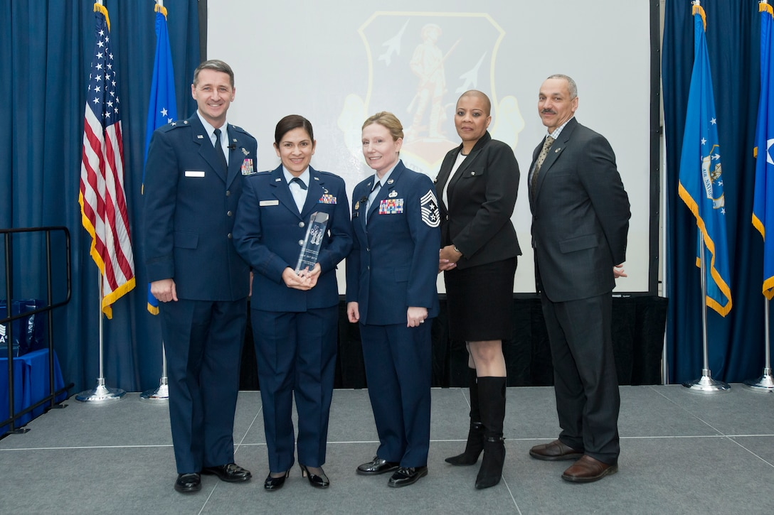 Capt. Janisse Rivera (second from left) is presented with the Air National Guard Readiness Center Company Grade Officer of the Year award during the ANGRC annual awards ceremony held March 22, 2018, at the ANGRC on Joint Base Andrews, Md. (U.S. Air National Guard photo/Tech. Sgt. John E. Hillier)