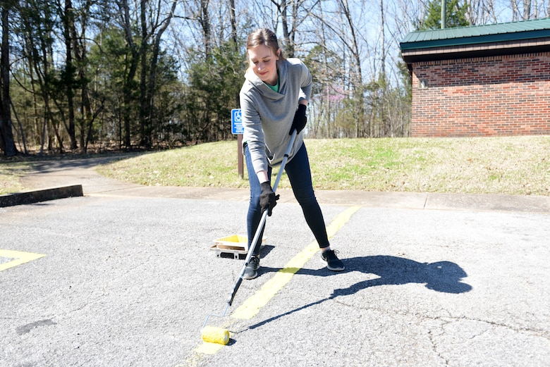Summer Dowdy, strategic planner with VF Solutions, paints parking spot stripes while volunteering for an early Earth Day clean-up event March 22, 2018 at Seven Points Campground on the shoreline of J. Percy Priest Lake in Hermitage, Tenn. Sixty VF Solutions employees partnered with the U.S. Army Corps of Engineers Nashville District to spruce up the popular campground ahead of the 2018 recreation season. (USACE photo by Lee Roberts)