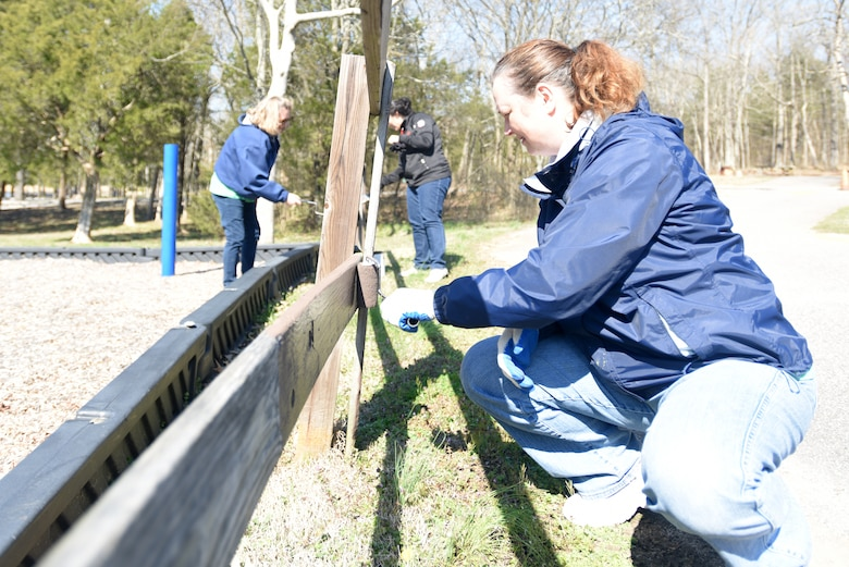 Marla Heath (Front), production planner; Dana Sanders (Back Left), strategic planner; and Jenny Brennan, forecast analyst; with VF Solutions, paint a playground fence while volunteering for an early Earth Day clean-up event March 22, 2018 at Seven Points Campground on the shoreline of J. Percy Priest Lake in Hermitage, Tenn. Sixty VF Solutions employees partnered with the U.S. Army Corps of Engineers Nashville District to spruce up the popular campground ahead of the 2018 recreation season. (USACE photo by Lee Roberts)