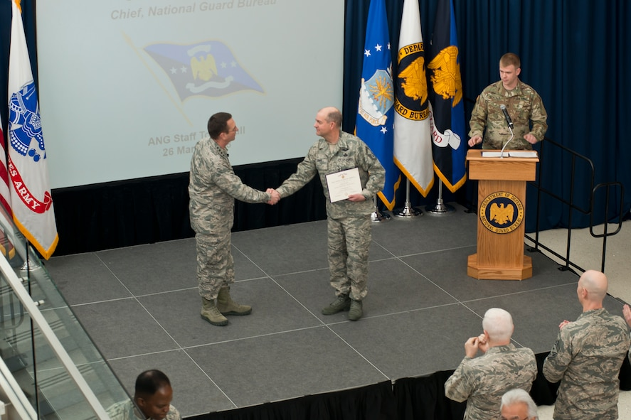 Senior Master Sgt. Chad Jones is presented with the Defense Meritorious Sevice Medal by Gen. Joseph Lengyel, Chief, National Guard Bureau, during a town hall event at the Air National Guard Readiness Center on Joint Base Andrews, Md., March 26, 2018. (U.S. Air National Guard photo/Tech. Sgt. John E. Hillier)