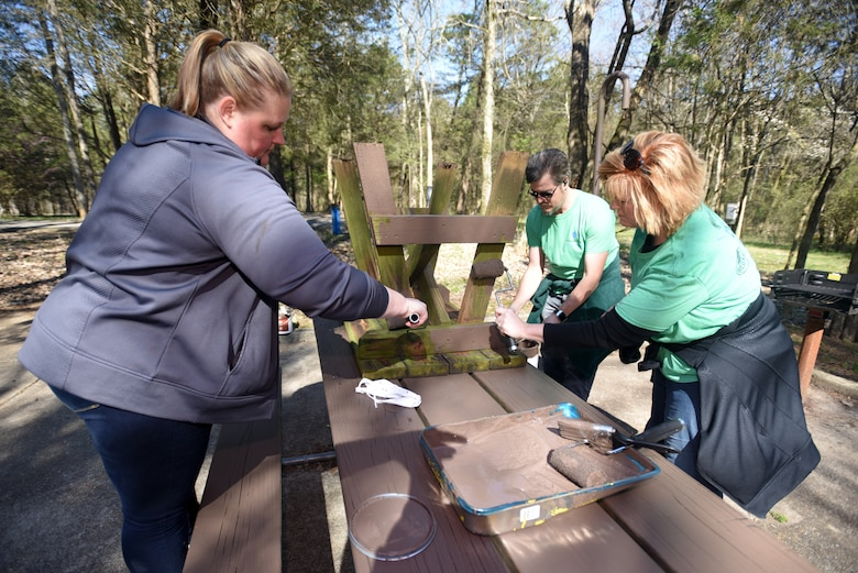 Helen Hicks (Left), senior program manager; Amy Morris, program manager; and Chris Bennett, reporting manager, with VF Solutions, paint a campsite table while volunteering for an early Earth Day clean-up event March 22, 2018 at Seven Points Campground on the shoreline of J. Percy Priest Lake in Hermitage, Tenn. Sixty VF Solutions employees partnered with the U.S. Army Corps of Engineers Nashville District to spruce up the popular campground ahead of the 2018 recreation season. (USACE photo by Lee Roberts)
