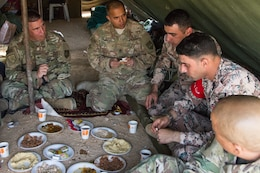 Soldiers from the Jordan Armed Forces Noncommissioned Officer Academy share a meal with U.S. Soldiers from the 648th Military Engagement Team, Georgia Army National Guard, during the culminating exercise of the JAF NCOA Squad Leader Course, March 19, 2018, near Amman, Jordan. The 648th MET advised JAF NCOA instructors as the Jordanian leaders developed the program of instruction for the course, which is attended by their soldiers and their regional allies.