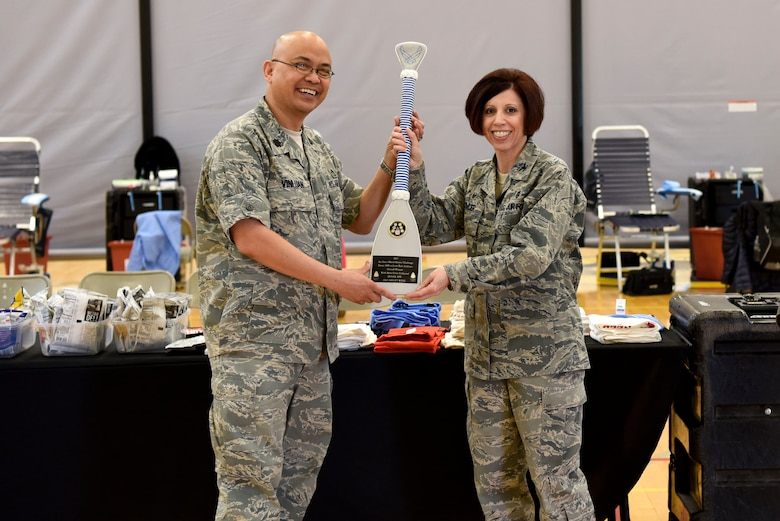 Lt. Col. Jerome Vinluan, Armed Services Blood Program deputy director, presents Col. Patricia Fowler, 436th Medical Group commander, with an award for winning a blood drive challenge March 19, 2018, at Dover Air Force Base, Del. The challenge took place last quarter against Joint Base Andrews, Md. (U.S. Air Force Photo by Airman 1st Class Zoe M. Wockenfuss)