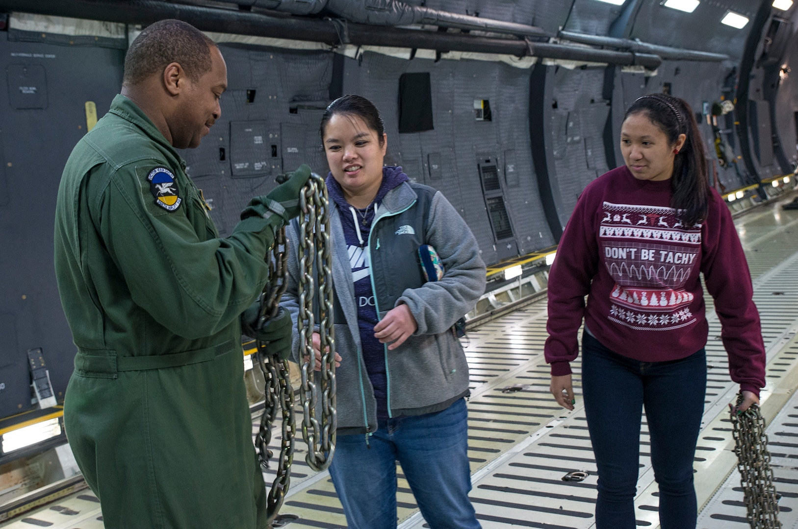 Master Sgt. Bryan Boyd (left), 356th Airlift Squadron loadmaster, shows touring visitors the different chains used to tie down cargo during a walk-through tour of a C-5M Super Galaxy aircraft Dec. 18, 2017 at Joint Base San Antonio-Lackland, Texas. The visitors also toured the C-5 flight simulator at the 733rd Training Squadron.