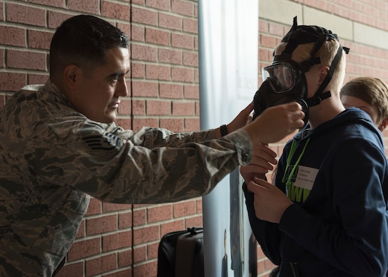 Staff Sgt. Gerardo Salas, 92nd Medical Group Bioenvironmental engineer, helps Dustin Ylitalo, Deer Park Middle School student, with a M50 gas mask at an informational booth during the  Eastern Washington Regional Science and Engineering Fair at the Spokane Washington State University campus, Washington, March 15, 2018. Members of Team Fairchild attended the fair to provide visiting students with information about the science, technology, engineering and math related fields that the U.S. Air Force offers. (U.S. Air Force photo/Senior Airman Ryan Lackey)