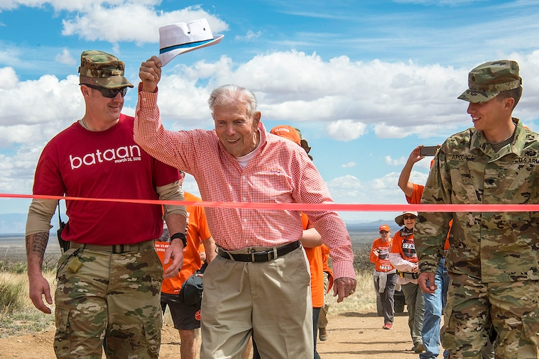 A 100-year-old retired Army colonel and Bataan Death March survivor raises his hat as he crosses the finish line of an event.