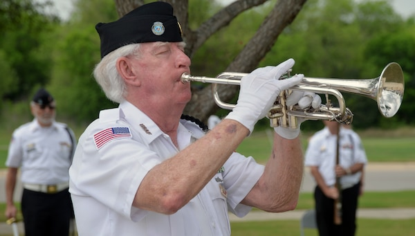 "A member of the Fort Sam Houston Memorial Services Detachment plays ""Taps"" near the end of the ceremony for the 50th Anniversary of the Commemoration of the Vietnam War at the Fort Sam Houston National Cemetery March 27."