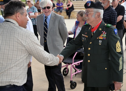 Retired Command Sgt. Maj. Felipe O'Bryan receives an official Vietnam lapel pin at the end of the ceremony for the 50th Anniversary of the Commemoration of the Vietnam War at the Fort Sam Houston National Cemetery March 27.