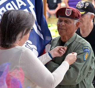 A retired Army Special Forces sergeant major steps up to receive his Vietnam service lapel pin at the conclusion of the 50th Anniversary of the Commemoration of the Vietnam War at the Fort Sam Houston National Cemetery March 27.