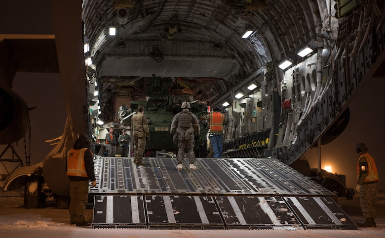 U.S. Air Force Airmen and U.S. Army Soldiers work together to load an Interim Armored Vehicle Stryker into a C-17 Globemaster III during Exercise Artic Pegasus at Elmendorf Air Force Base, Alaska, March 13, 2018. The purpose of the exercise was to practice cold-weather operations in Deadhorse, Alaska. (U.S. Air Force photo by Senior Airman Tryphena Mayhugh)