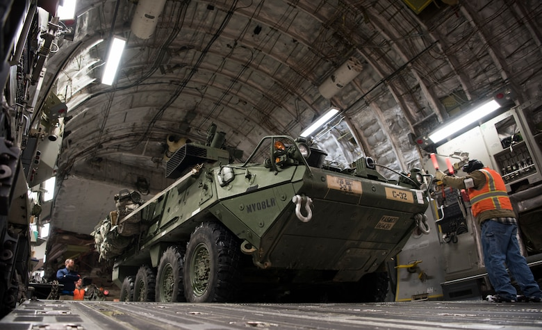 Danny Batchelor, 445th Expeditionary Aerial Port Squadron nightshift foreman, directs a U.S. Army Interim Armored Vehicle Stryker onto a C-17 Globemaster III at Elmendorf Air Force Base, Alaska, March 13, 2018. Airmen assigned to the 62nd Airlift Wing participated in the exercise to practice cold-weather operations. (U.S. Air Force photo by Senior Airman Tryphena Mayhugh)