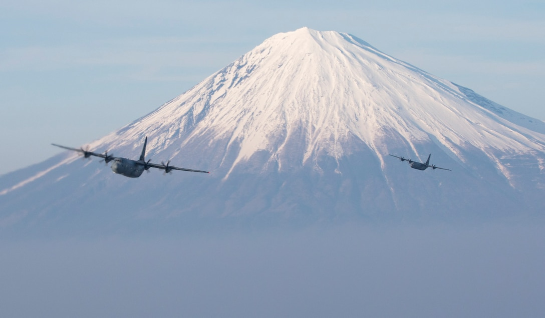 Two Air Force C-130J Super Hercules' assigned to the 36th Airlift Squadron fly near Mount Fuji