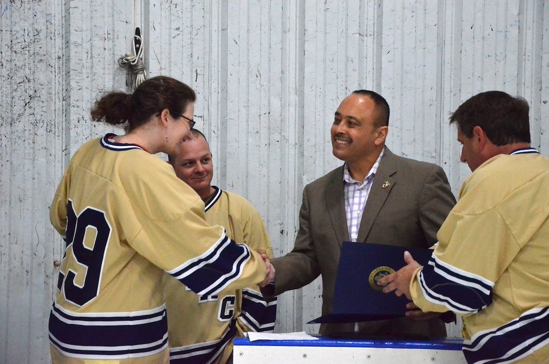 Master Sgt. Rebecca Goodwin, a member of the Athletes for Teamwork and Charity hockey team at Patrick AFB, Fla., shakes the hand of Rob Medina, Director of Community Relations for Congressman Bill Posey (FL-15), where Media presented Certificates of Appreciation to the players for their fundraising efforts.  Also pictured are Tech. Sgt. Denton Kimber (second from left) and team captain Bill Hungate (right).  (U.S. Air Force photo by Susan A. Romano)