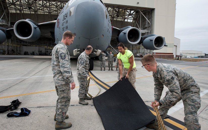 """Airmen from the 437th Aircraft Maintenance Squadron and Mark Kirsch, strong man for """"Man vs. Impossible,"""" setup for a practice session of pulling a C-17 Globemaster III from a hangar at Joint Base Charleston, S.C., March 27, 2018."""