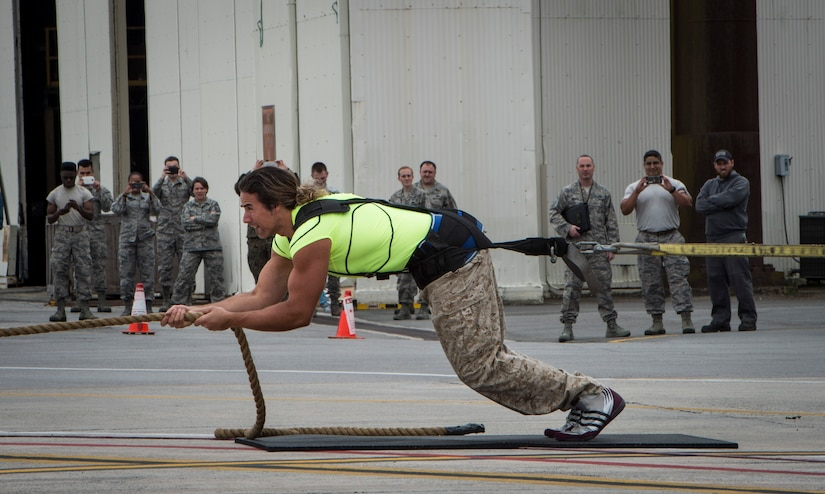 """Mark Kirsch, strong man for """"Man vs. Impossible,"""" pulls a C-17 Globemaster III from a hangar at Joint Base Charleston, S.C., March 27, 2018."""