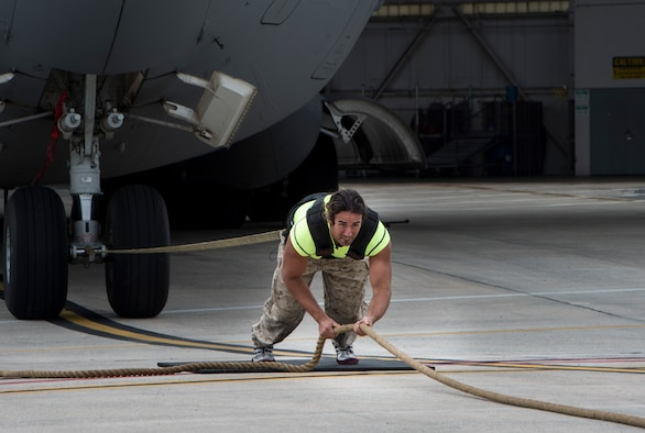"Mark Kirsch, strong man for ""Man vs. Impossible,"" pulls a C-17 Globemaster III from a hangar at Joint Base Charleston, S.C., March 27, 2018."