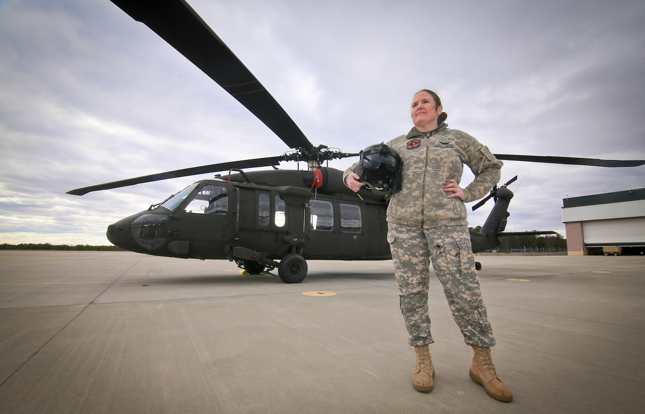 A soldier stands in front of a UH-60L Black Hawk helicopter.