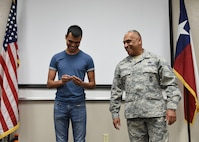Tech. Sgt. Manuel Mauricio, a member of the 149th Fighter Wing's Security Forces Squadron, Air National Guard, passes down his police badge to his son Nathaniel Mauricio