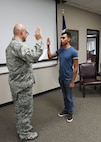 Lt. Col. John Pollard, the 149th Security Forces Squadron commander, swears Nathaniel Mauricio into the Air National Guard
