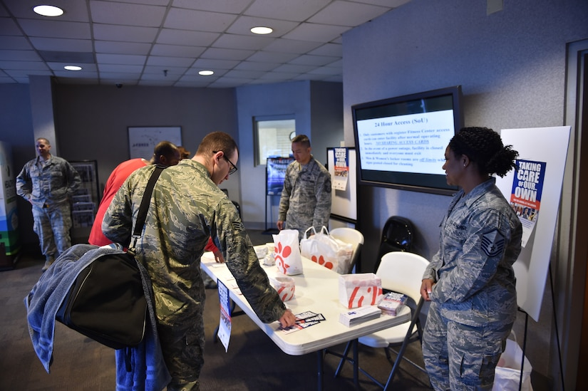 An Airman takes a pamphlet to learn more information about the Air Force Assistance Fund during the Joint Base Charleston AFAF Campaign kicked off March 27, 2018.