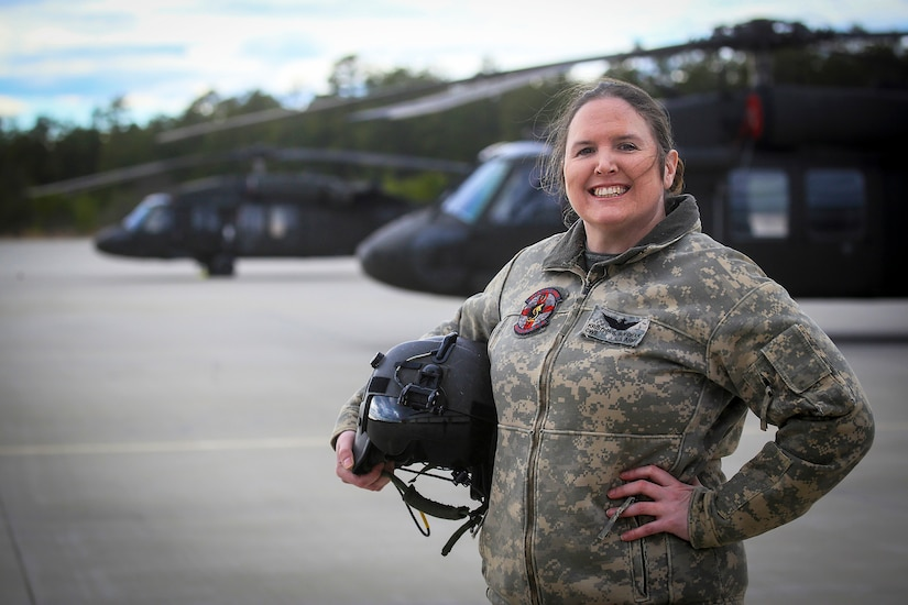 An airman stands in front of two helicopters.