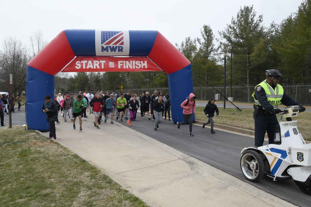 Runners and walkers leave the starting line at the annual 'Honor the Warrior' 5K event at the McNamara Headquarters Complex, Fort Belvoir, Virginia, March 28, 2018.