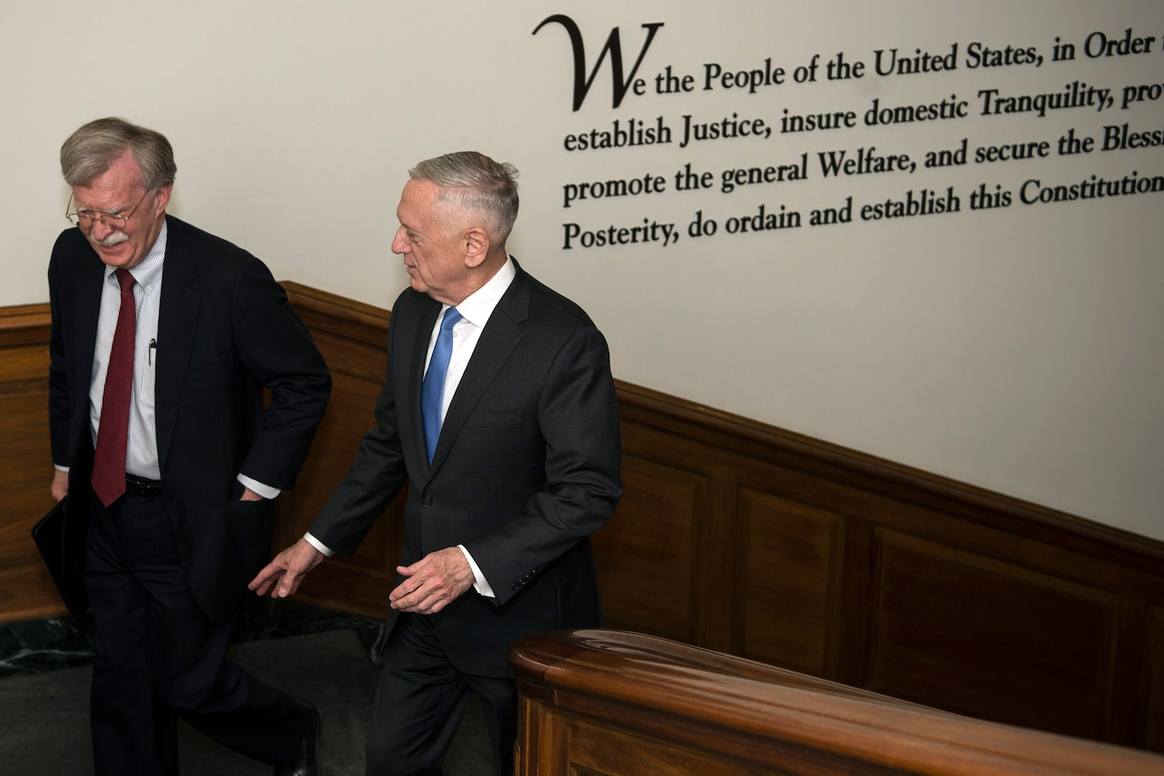 Defense Secretary James N. Mattis walks up the stairs with another person.