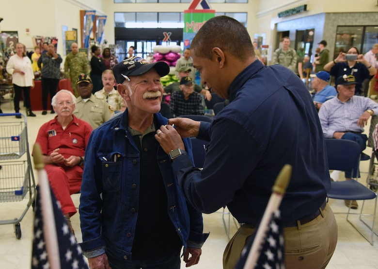 Gregory Hall, Keesler Base Exchange general manager, presents a lapel pin to Roger Anderson, U.S. Navy Vietnam veteran, during the 50th Anniversary Vietnam Memorial Pinning Day at The Exchange March 29, 2018, on Keesler Air Force Base, Mississippi. The event, which also included a cake cutting ceremony, was held to honor Vietnam veterans for their service. (U.S. Air Force photo by Kemberly Groue)