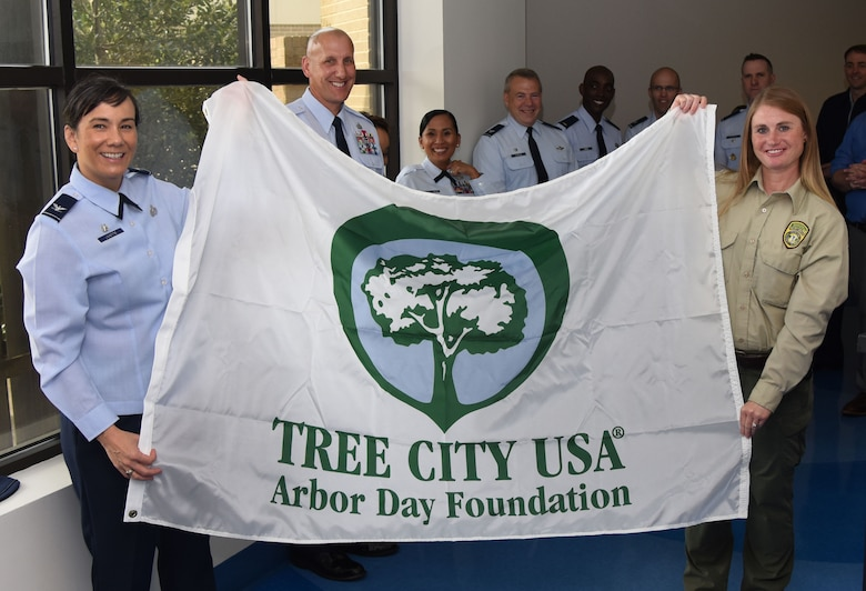 U.S. Air Force Col. Debra Lovette, 81st Training Wing commander, and Kelly Griffin, Harrison County Beautification Commission executive director, hold a Tree City USA flag during the Arbor Day Ceremony at the Keesler Child Development Center March 29, 2018, on Keesler Air Force Base, Mississippi. This is the 25th consecutive year Keesler has received the Tree City USA award. Arbor Day is a nationally celebrated observance that focuses on environmental issues and ways to improve the environment. (U.S. Air Force photo by Kemberly Groue)