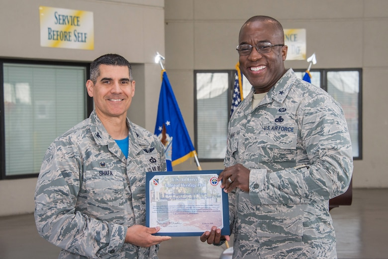 Col. Eric Shafa, 42nd Air Base Wing commander, presents Brig. Gen. Stacey T. Hawkins, Ogden Air Logistics Complex commander, Hill Air Force Base, Utah, with a certificate signifying the placement of a commemorative brick at the Air Force Enlisted Heritage Hall, Maxwell-Gunter Annex March 23, 2018. The AFEHH offers these bricks as a way to recognize a devoted career, to honor service or acknowledge the dedication of spouses, family members and others. (U.S. Air Force photo by William Birchfield)