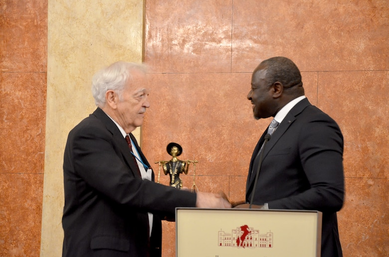 Dr. Lassina Zerbo (right), Executive Secretary for the Comprehensive Test Ban Treaty Organization in Vienna, presents Dr. Bob Kemerait, senior scientist at the Air Force Technical Applications Center, with a statue of a water carrier from Zerbo's home country of Burkina Faso, Africa.  Zerbo recognized Kemerait's perfect attendance at CTBTO's 50th Working Group B session March 19, 2018. No other member of any nation has attended all 50 WGB meetings.  (U.S. Air Force photo by Susan A. Romano)
