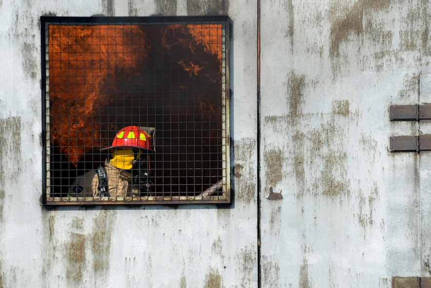 A 100th Civil Engineer Squadron firefighter extinguishes a fire inside a mock aircraft, as part of annual proficiency skill training at a burn pit at RAF Mildenhall, England, March 21, 2018. All firefighters are required to conduct live-fire training at least twice a year to stay proficient and keep their qualifications current. (U.S. Air Force photo by Tech. Sgt. Emerson Nuñez)