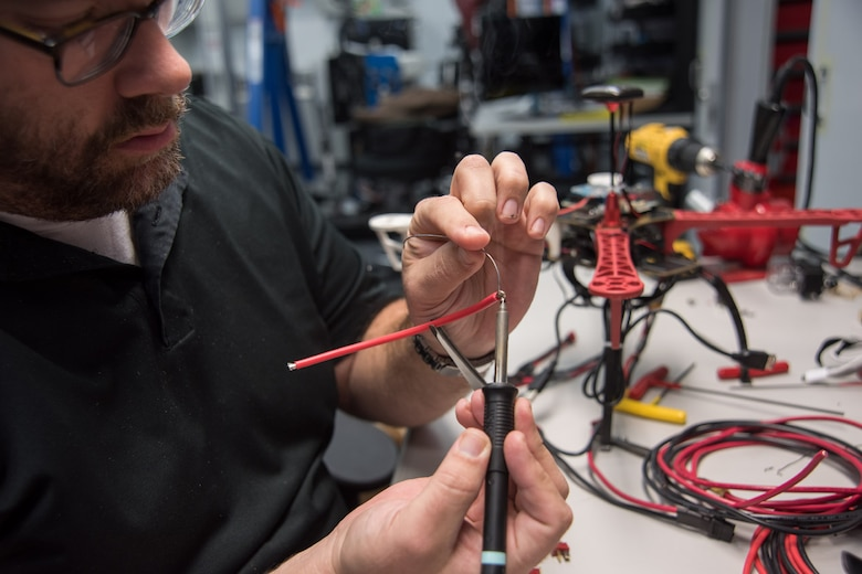 Space and Naval Warfare Systems Center (SSC) Atlantic employee Chad Sullivan tins the wire for a new battery lead to install on an unmanned aerial vehicle (UAV). Sullivan is a member of the SSC Atlantic Unmanned Systems Research (SAUSR) Range team which is working with the Defense Advanced Research Projects Agency (DARPA) to get autonomous technology in the hands of warfighters. SSC Atlantic develops, acquires and provides life cycle support for command, control, communications, computer, intelligence, surveillance and reconnaissance (C4ISR) systems, information technology and space capabilities. A leading-edge Navy engineering center, SSC Atlantic designs, builds, tests, fields and supports many of the finest frontline C4ISR systems in use today, and those being planned for the future.
