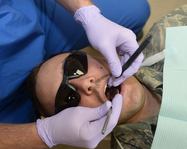 Staff Sgt. William Garrett, a 28th Medical Group Dental Clinic dental technician, checks the teeth of Tech. Sgt. Michael Wilde, the 28th MDG noncommissioned officer in charge of clinical support, during an appointment at Ellsworth Air Force Base, S.D., March 6, 2018. The dental clinic at Ellsworth AFB has been in operation since 1948. (U.S. Air Force photo by Airman 1st Class Thomas Karol)